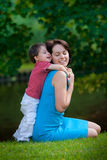 Two years old boy hugs his young mom in park. Cute two years old boy hugs his young mom in park royalty free stock photos