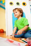 Tie for creative activity. Two years old boy painting with watercolors sitting on the floor in kids room stock images