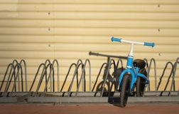 Two years old boy parking his blue bicycle without pedals in a bike park royalty free stock photo