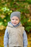 Two years old boy standing on falling autumn leaves. Two years old boy in vest and cap standing on falling autumn leaves royalty free stock photography