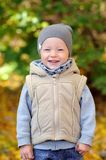 Two years old boy standing on falling autumn leaves. And smiling stock photography