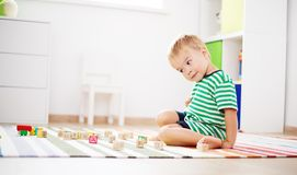 Two years old child sitting on the floor with wooden cubes. Two years old child sitting on the floor. Pretty little boy palying with wooden cubes at home Stock Images