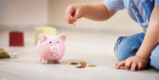 Two years old child sitting on the floor and putting a coin into a piggybank Stock Photo