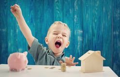 Two years old child sitting on the floor and putting a coin into a piggybank. Three years old child sitting st the table with money and a piggybank. Happy boy stock image