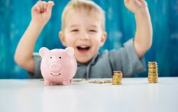 Two years old child sitting on the floor and putting a coin into a piggybank Stock Photos