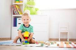 Two years old child sitting on the floor with wooden cubes. Happy two years old child sitting on the floor with toys. Pretty little boy palying with wooden cubes Royalty Free Stock Photography