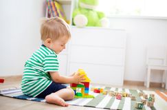 Two years old child sitting on the floor with wooden cubes. Happy two years old child sitting on the floor with toys. Pretty little boy palying with wooden cubes Stock Image