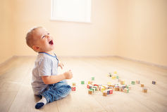 Two years old child sitting on the floor with wooden cubes. Two years old child sitting on the floor. Pretty little boy palying with wooden cubes at home Stock Photo