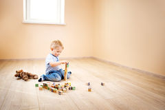 Two years old child sitting on the floor with wooden cubes. Two years old child sitting on the floor. Pretty little boy palying with wooden cubes at home Stock Photos