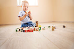 Two years old child sitting on the floor with wooden cubes. Two years old child sitting on the floor. Pretty little boy palying with wooden cubes at home Royalty Free Stock Image