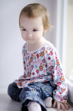 Two years old girl sitting by the window royalty free stock images
