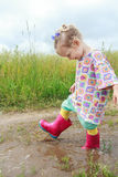 Two years old preschooler girl having fun walking. Two years old preschooler girl is having fun walking summer field puddle stock image