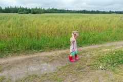 Two years old preschooler girl playing on farm dirt road near puddle Royalty Free Stock Photography