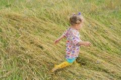 Two years old preschooler girl running on annual plants field covering. Two years old preschooler girl is running on annual plants field covering stock photo
