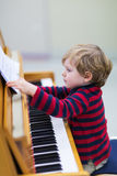 Two years old toddler boy playing piano Royalty Free Stock Image