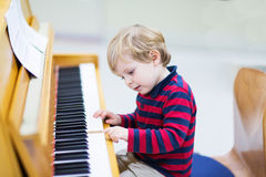 Two years old toddler boy playing piano, music schoool.