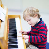 Two years old toddler boy playing piano, music schoool. Royalty Free Stock Images
