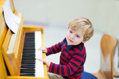 Two years old toddler boy playing piano, music schoool. Royalty Free Stock Photos