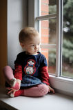 Two years old toddler girl by the window Stock Photos