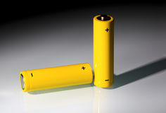 Two yellow AA-size batteries in light beam. Royalty Free Stock Photo