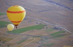 Two air balloons flying over the land stock photo