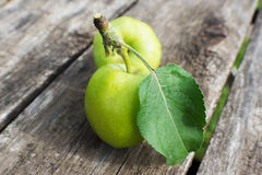 Two yellow apples with leaves on wooden table Stock Images