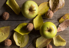 Two yellow apples, walnuts and autumn leaves on wood Royalty Free Stock Photos