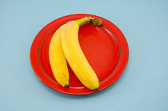 Two yellow banana in red plate Stock Photo