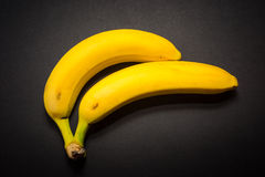 Two yellow bananas on the black background Royalty Free Stock Photo