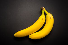 Two yellow bananas on the black background Royalty Free Stock Image