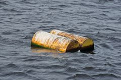 Two yellow barrels drift on water Royalty Free Stock Images