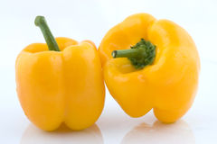 Two yellow bell peppers. Two yellow bell peppers againsta white background Royalty Free Stock Photo