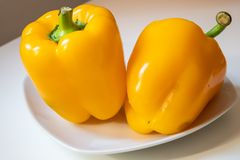 Two yellow bell peppers on the white porcelain dish closeup - Image stock image