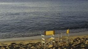 Two yellow chairs on a sandy beach. Still life photography of two yellow chairs on a sandy beach Stock Image
