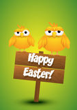 Two yellow chicks standing on a wooden Easter sign. Royalty Free Stock Photography