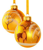 Two yellow Christmas balls. With images of deer and snow covered tree hanging on a golden ribbons. Isolated on a white background with clipping path Stock Photos