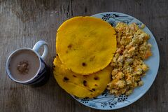 Two yellow corn arepas, with scrambled egg