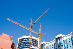 Two yellow cranes. At a house under construction Stock Photo