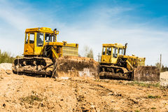 Two yellow dirty old bulldozer stand on a construction site on a sunny day against a background of blue sky Stock Photos