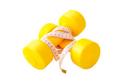 Two yellow dumbbells and tape measure isolated on the white back Royalty Free Stock Image