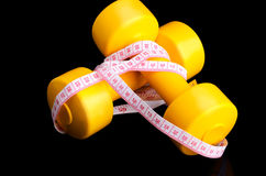 Two yellow dumbbells and tape measure lying on a black backgroun Royalty Free Stock Photo