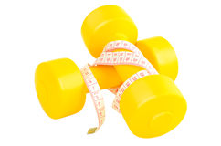 Two yellow dumbbells and tape measure lying on the white backgro Royalty Free Stock Photos