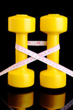 Two yellow dumbbells and tape measure placed vertically on black Stock Photo