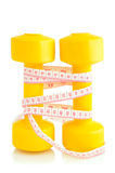 Two yellow dumbbells and tape measure placed vertically isolated Royalty Free Stock Photography