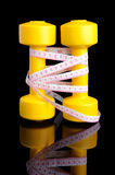 Two yellow dumbbells and tape measure placed vertically with ref Stock Photos