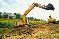Two yellow excavators excavating on riverbed Stock Photography