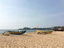 Two yellow fishing boats on empty beach Stock Photos