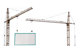 Two yellow hoisting cranes. And advertisement hoarding isolate on white background Stock Image