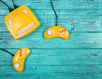 Two yellow joystick and game console on a blue wooden background. Top view. Flat lay Royalty Free Stock Images