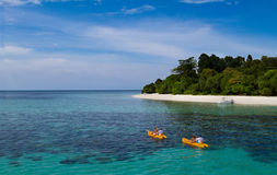 Two yellow kayaks next to a tropical exotic island. With blue transparent water Royalty Free Stock Photography